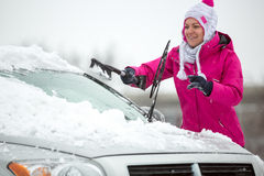 Woman cleaning car of snow Royalty Free Stock Images