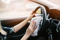 Woman cleaning car steering wheel. Modern car interior Royalty Free Stock Image