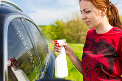 Woman Cleaning Car Windows with Spray Cleaner Royalty Free Stock Photos