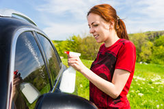 Woman Cleaning Car Windows with Spray Cleaner Stock Photography