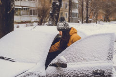 Woman cleaning car windshield of snow Stock Image