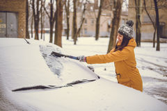 Woman cleaning car windshield of snow Stock Photos