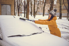 Woman cleaning car windshield of snow Stock Images