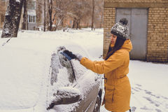 Woman cleaning car windshield of snow Royalty Free Stock Image