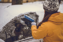 Woman cleaning car windshield of snow Stock Photo