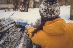 Woman cleaning car windshield of snow Royalty Free Stock Photography