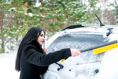 Woman cleaning car windshield of snow winter happy young scraper Stock Images