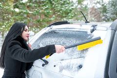 Woman cleaning car windshield of snow winter happy young scraper Royalty Free Stock Photos