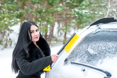 Woman cleaning car windshield of snow winter happy young scraper Royalty Free Stock Image