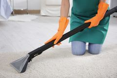 Woman cleaning carpet with cleaner. Woman cleaning carpet with vacuum cleaner Royalty Free Stock Images