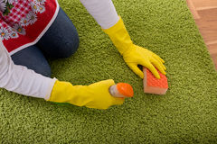 Woman cleaning carpet Stock Photos