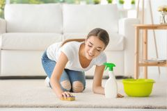 Woman cleaning carpet in room stock photos