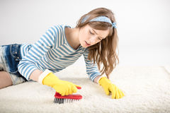 Woman cleaning carpet. Young woman in rubber gloves cleaning carpet with brush Stock Images