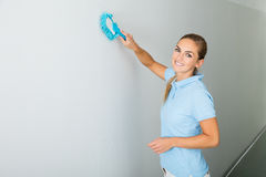 Woman Cleaning The Ceiling With Mop. Young Woman Cleaning The Ceiling With Mop On The Corridor Of The Building Stock Photo
