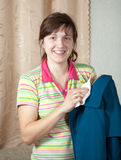 Woman cleaning coat. With washrag  at home Royalty Free Stock Photography