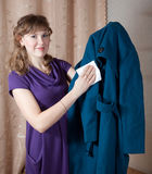 Woman cleaning coat. With rag  at home Royalty Free Stock Image