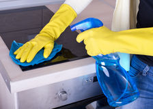 Woman cleaning cooker Stock Image