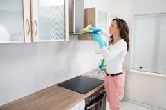 Woman Cleaning Cooker Hood stock images
