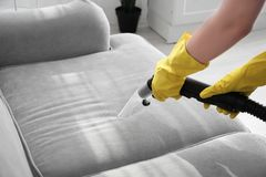 Woman cleaning couch with vacuum cleaner. At home Stock Photo