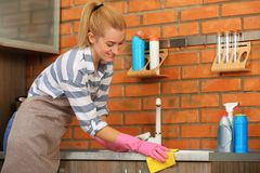 Woman cleaning counter with rag. In kitchen royalty free stock photography