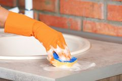 Woman cleaning counter with sponge in kitchen. Closeup stock photos