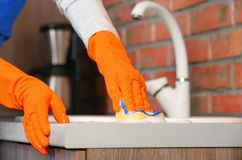Woman cleaning counter with sponge in kitchen. Closeup royalty free stock photo