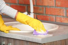 Woman cleaning counter with sponge in kitchen. Closeup royalty free stock images