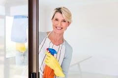 Woman cleaning door glass Stock Image