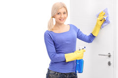 Woman cleaning a door with rag Royalty Free Stock Images