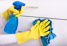 Woman cleaning drawers. Close up of female hand with rubber gloves and detergent in sprayer cleaning drawers Royalty Free Stock Images