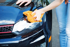 Woman cleaning , drying car with microfiber cloth Royalty Free Stock Photos