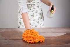 Woman cleaning dusty wooden desk Stock Photo