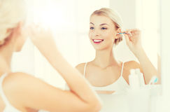 Woman cleaning ear with cotton swab at bathroom. Beauty, hygiene and people concept - smiling young woman cleaning ear with cotton swab and looking to mirror at Royalty Free Stock Photo