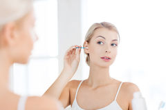 Woman cleaning ear with cotton swab at bathroom Royalty Free Stock Image