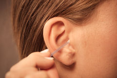 Woman cleaning ear with cotton swabs closeup. Hygiene concept. Woman cleaning ear with cotton swabs closeup stock images