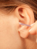 Woman cleaning ear with cotton swabs closeup. Hygiene concept. Woman cleaning ear with cotton swabs closeup stock photo