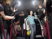 Woman With Cleaning Equipment Posing In Front Of Paparazzi Stock Photo