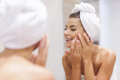 Woman cleaning face. Woman removing pimple from her face Royalty Free Stock Image