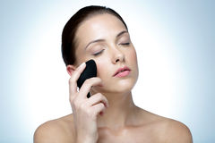 Woman cleaning face with spa stone Royalty Free Stock Image
