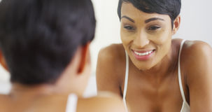 Woman cleaning face with water and looking in mirror. Black woman cleaning face with water and looking in mirror Stock Image