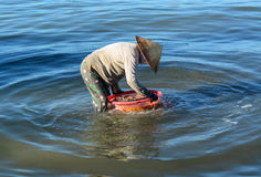 A woman cleaning fish on the sea in Cam Ranh bay, Vietnam.  stock image