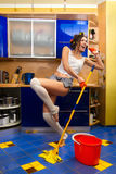 Woman cleaning the floor. Smiling young woman cleaning the floor at home and singing Royalty Free Stock Image