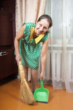 Woman cleaning floor with dustpan Royalty Free Stock Photography
