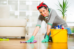 Woman cleaning the floor while kneeling Royalty Free Stock Images