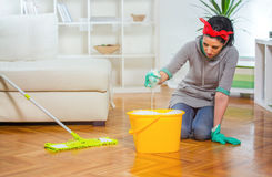 Woman cleaning the floor while kneeling Royalty Free Stock Photography