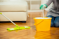 Woman cleaning the floor while kneeling at home Royalty Free Stock Image