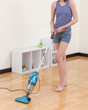 Woman cleaning the floor with vacuum cleaner Stock Photography