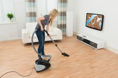 Woman Cleaning Floor With Vacuum Cleaner Royalty Free Stock Photography