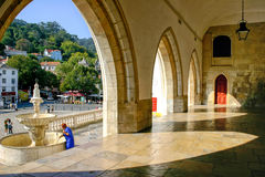 Woman cleaning a fountain in Sintra, Portugal. A woman in a blue dress cleans a fountain and is framed by a backdrop of high-arched doorways in the hilltop Royalty Free Stock Images