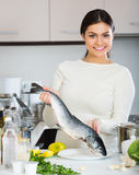 Woman cleaning fresh rainbow trout. Young woman in white sweater cleaning fresh rainbow trout Stock Photos